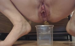 Shaved babe shits in a glass